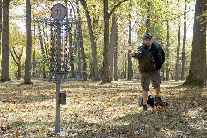 A man playing disc golf as he tosses a frisbee into a chain net outside
