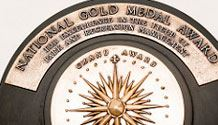 "Circular award with gold embellishments. Plaque reading ""National Gold Medal Award"" towards to"